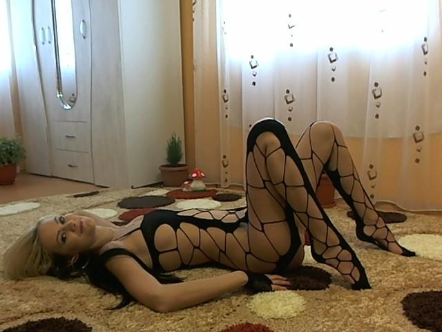Delia_xoxo from MyFreeCams laying on the floor on black fishnet lingerie