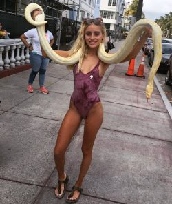 Naomi Woods in swimsuit with giant snake on public street