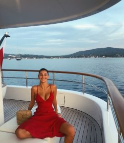 smiling Camila Morrone on boat wearing red dress