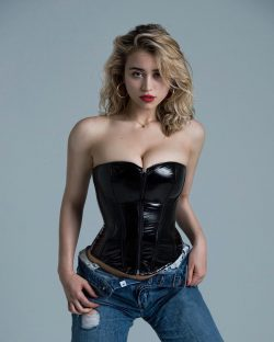 actress Caylee Cowan in leather corset & jeans